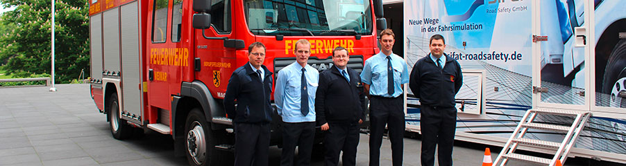 Feuerwehrmänner vor einem Feuerwehrfahrzeug und einem Simulator SiFaT